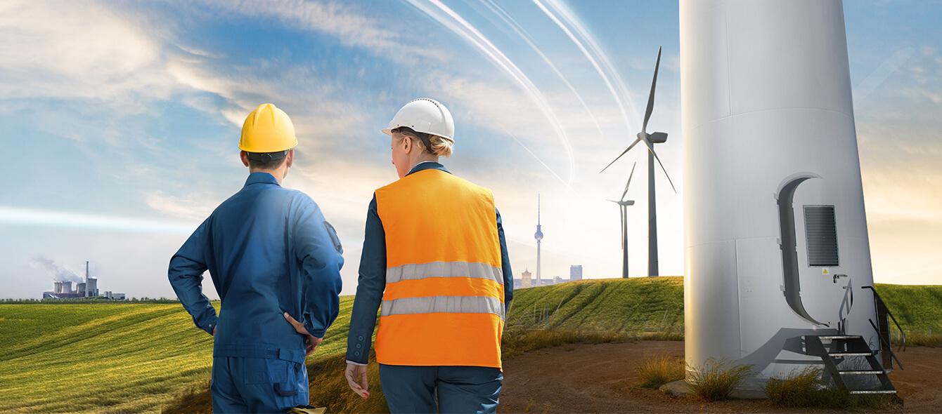enformer Stimmungsbild Rückenansicht Arbeitende mit Blick auf Landschaft neben Fuß von Windkraftanlage Kraftwerke im Hintergund
