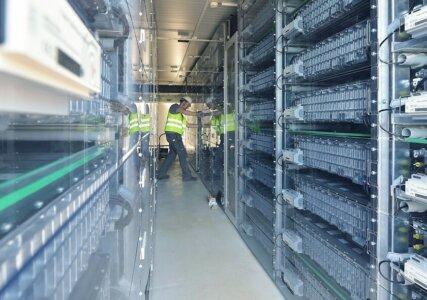Energiespeicher im enformer Arbeiter im Inneren einer Batteriespeicheranlage