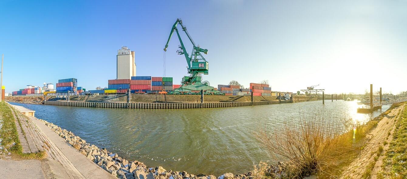Kran an einem Hafen verlädt farbige Container