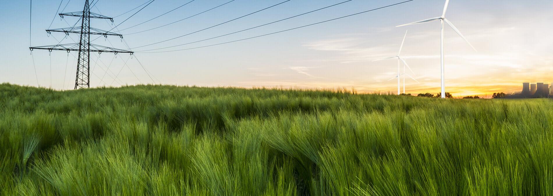 enformer Energiewende grüne Feldlandschaft Stommast Windkraftanlage Kohlekraftwerk im Hintergund