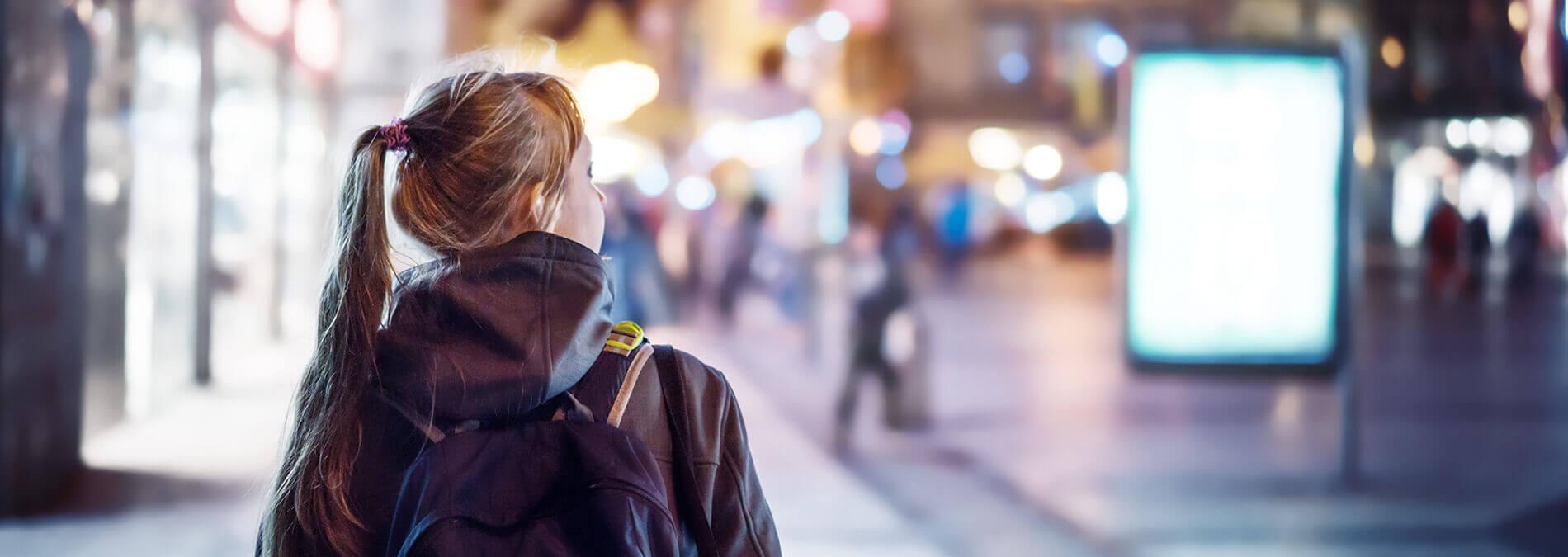 Mädchen von hinten in einer Stadt am Abend
