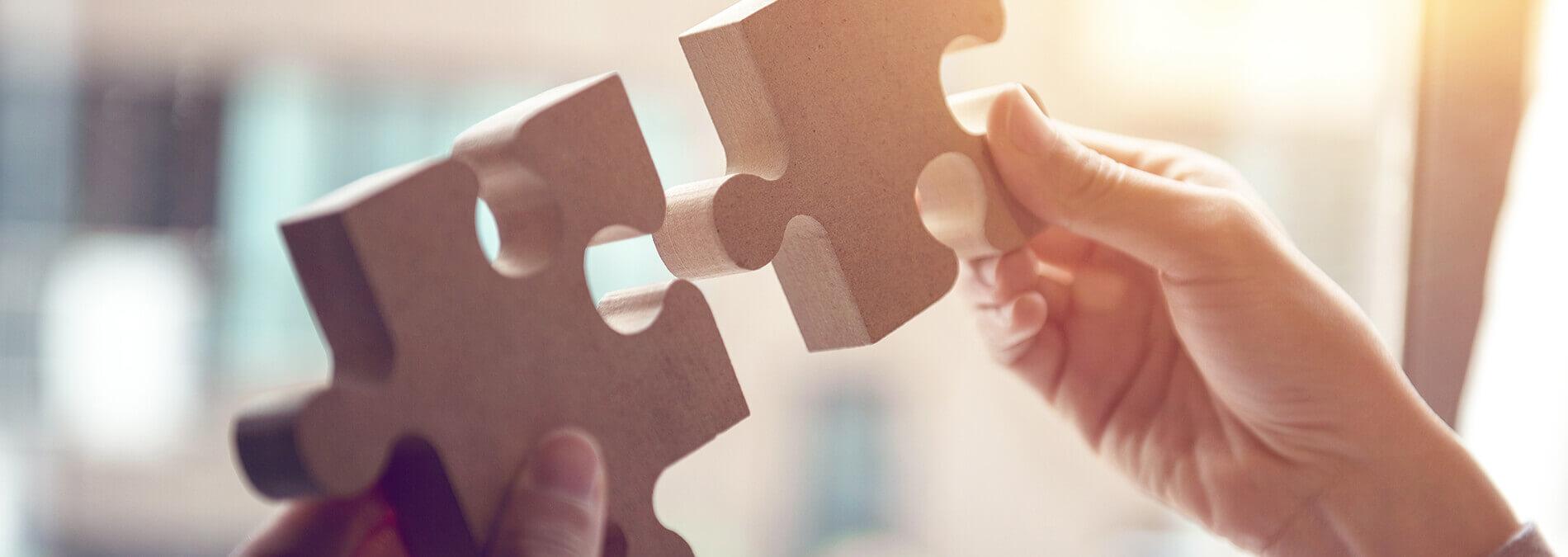enformer Sektorenkopplung Hand hält zwei passende Puzzleteile