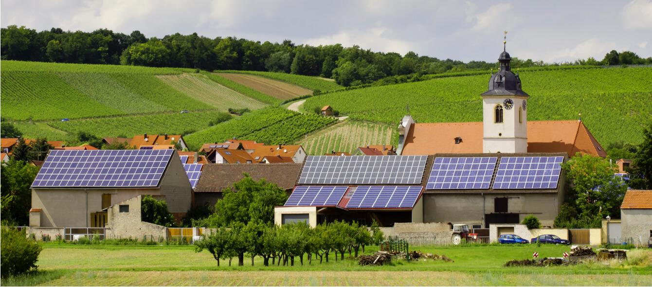 Energiewende im enformer Stimmungsbild Dorf mit Solardächern in hügeliger Feldlandschaft