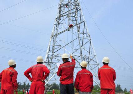Energiewende im enformer Rückenansicht Arbeiter bei Konstruktion eines Strommasten