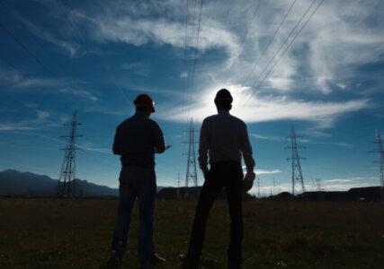 Stimmungsbild Silhouetten zweier Ingenieure vor Strommasten und bewegtem Himmel