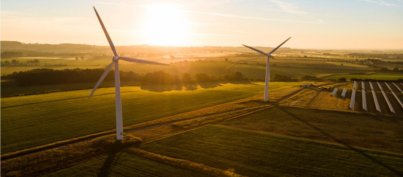 Stimmungsbild Drohnenaufnahme Windkraftanlagen und Solarpanels auf Feldern bei Sonnenaufgang