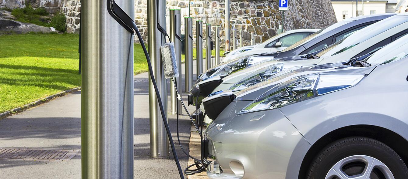 Sektorenkopplung im enformer Elekrtoautos vor Ladestationen