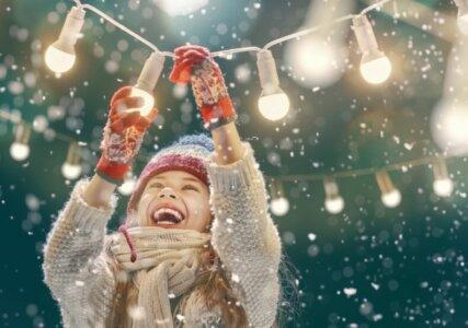 Stimmungsbild lachendes Kind mit Lichterkette bei Schnee