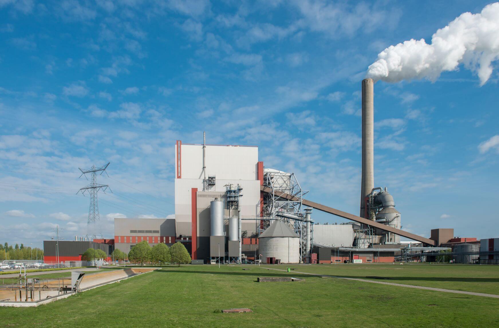 Aufnahme Kraftwerk Amer für Biomasse und Steinkohle vor grüner Wiese mit rauchendem Schornstein