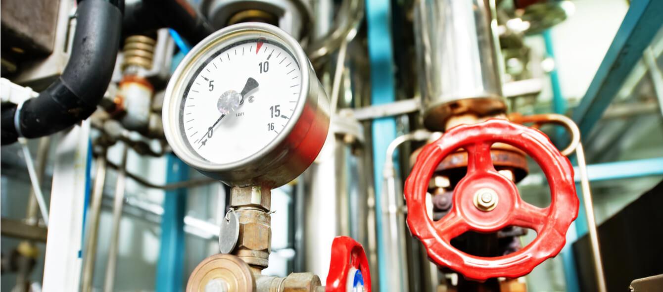 Energiewende im enformer Nahaufnahme eines Manometers sowie der Rohre und Hahnventile eines Heizungssystems
