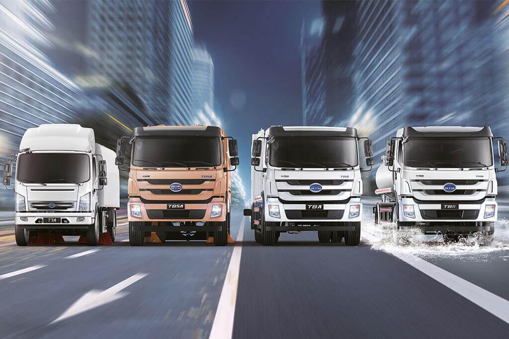 Stimmungsbild Frontalansicht vier fahrende Elekto Trucks von BYD in Stadt bei verschwommenem Hintergrund