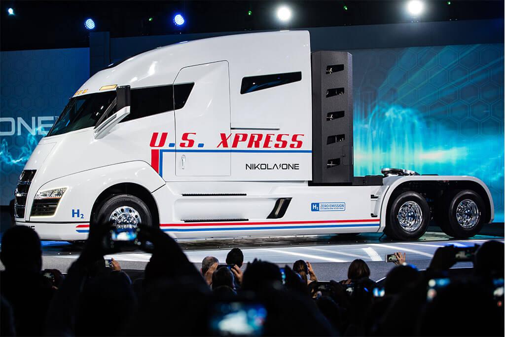Weißer Elektro Truck Nikola One mit rotem Schriftzug in Messehalle