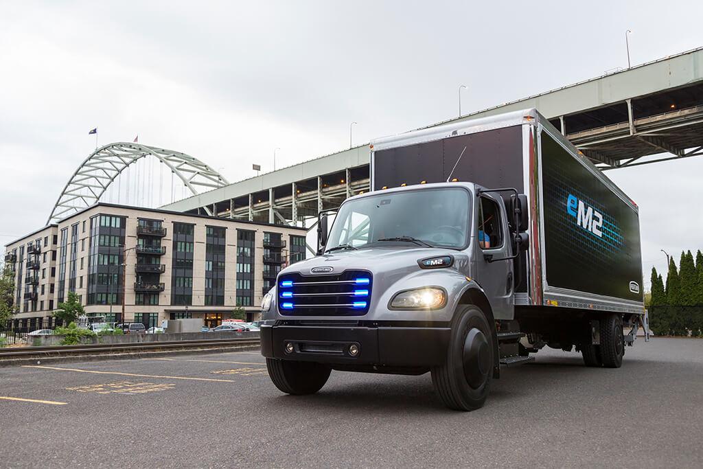 E-Truck mit blendenden Lichtern vor einer Brücke