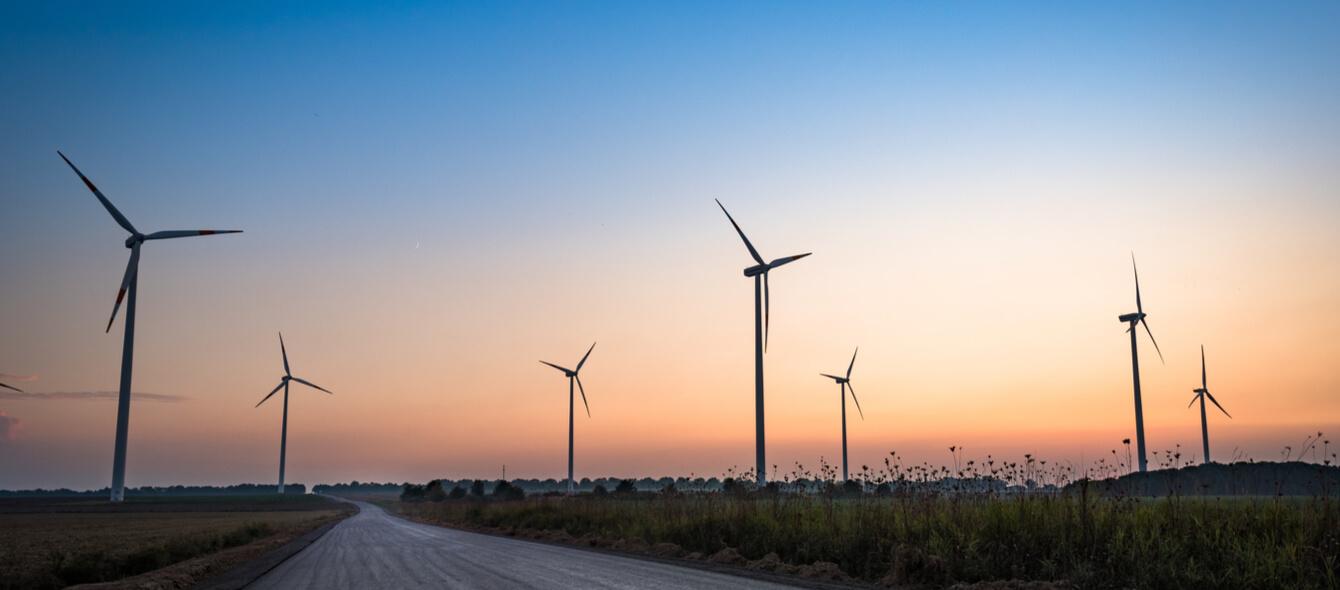 Windräder links und rechts einer Straße bei untergehender Sonne
