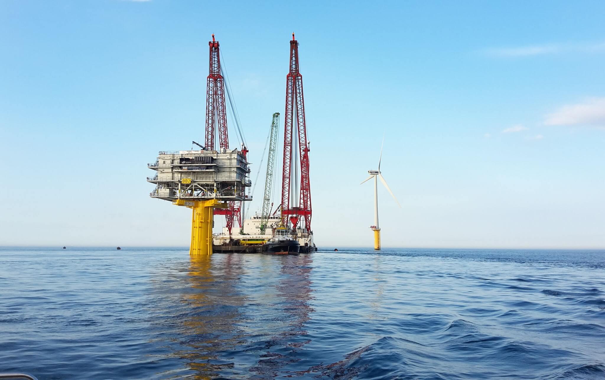 Ein Kranschiff errichtet neue Offshore-Windkraftanlagen