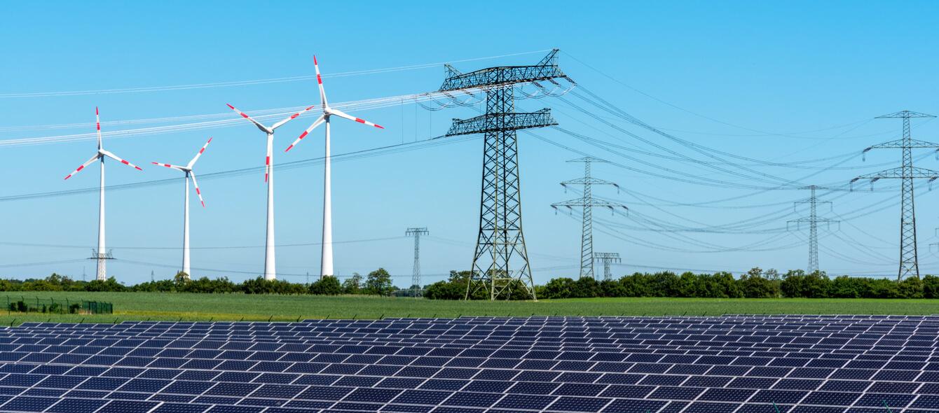 Solaranlagen und Windräder als Erneuerbare Energien in Verbindung mit Stromleitungen zum Weitertransport