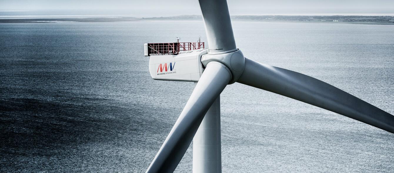 Rotorblätter einer Windkraftanlage in Nahaufnahme, im Hintergrund das Meer