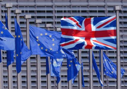 Die britische Flagge, der Unionjack, im Vordergrund weht in eine andere Richtung als die Flaggen der EU im Hintergrund