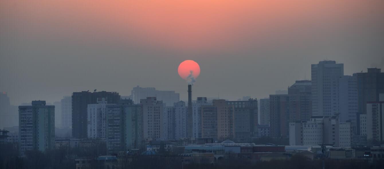 Chinesische Stadt in Smog vor Sonnenuntergang